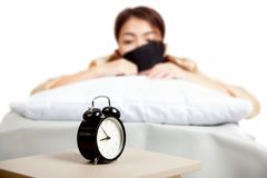 Allarm clock with sleepy Asian girl Stock Photo