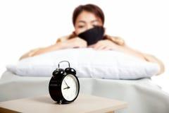 Allarm clock with sleepy Asian girl. Isolated on white background Stock Photo