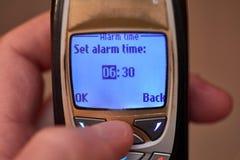 Allarme della regolazione sul vecchio cellulare Immagine Stock
