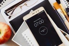Allarme sullo smartphone che suonano a sette di mattina, sui rifornimenti di scuola, sui vetri e sulla mela fotografie stock libere da diritti