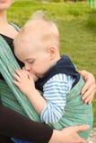 Allattando al seno in imbracatura del bambino all'aperto immagini stock