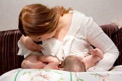 Allattar al senoe i bambini gemellati con il dispositivo per alimentarsi immagine stock libera da diritti