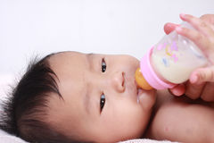 Allattare con il biberon asiatico sveglio della neonata Fotografia Stock