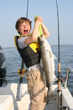 Allboy. Max hoists a striped bass he caught on Chesapeake Bay Royalty Free Stock Image