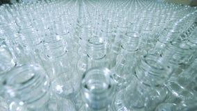 Alldeles av glasflaskor på en transportör, alkoholiserad produktion arkivfilmer