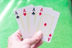 Alle Asse in der Hand mit einem Hintergrund der grünen Tabelle stockfotografie
