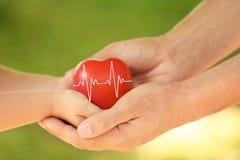Alle Typen Versicherung Glückliche Familie, die rotes Herz hält lizenzfreie stockfotos