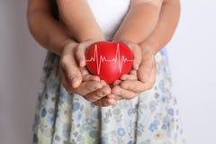 Alle Typen Versicherung Glückliche Familie, die rotes Herz hält stockbilder