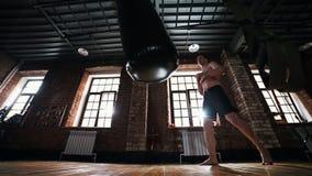 Alleen bokser die een ponsenzak in donkere gymnastiek schoppen stock video