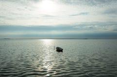 Alleen boot op Denemarken fyord op overzees met bewolkte hemel Stock Foto's