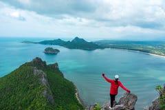 Alleen jong vrouwensucces die bovenop berg met overzees wandelen en Royalty-vrije Stock Foto's