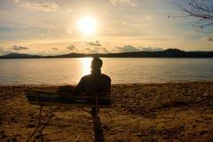 Alleen Jonge Mens in Silhouetzitting in The Sun op Strand De toerist neemt rust op houten bank bij de herfstmeer stock afbeeldingen