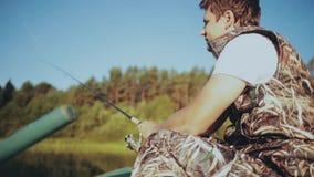 Alleen jonge mensenzitting in de rubberboot en visserij bij het meer Het mannetje houdt de hengel en verdraait spinnende spoel stock videobeelden