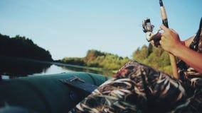 Alleen jonge mensenzitting in de rubberboot en visserij bij het meer Het mannetje houdt de hengel, vangt de bijtende vissen stock video
