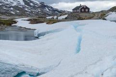 Alleen rustiek huis in sneeuw en ijsbergen Stock Fotografie