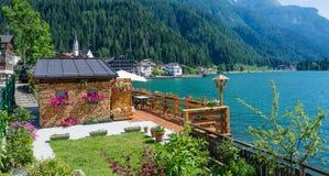 Alleghe, Belluno, Italia: un paesino di montagna affascinante situato in una regolazione naturale unica che trascura il suo lago  Fotografie Stock Libere da Diritti