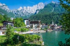 Alleghe Belluno, Italien: en charmig bergby som lokaliseras i en unik naturlig inställning som förbiser dess fascinerande sjö, i Royaltyfria Foton