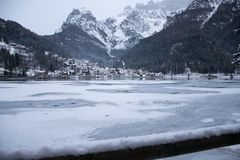 Alleghe with the frozen lake. Ice, snow, winter, cold, clouds, white, landscape, forests, trees, mountains Stock Photo