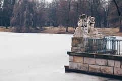 Allegory of the Vistula River by Ludwik Kauffman with frozen lake in Warsaw Royal Baths Park in winter royalty free stock photos