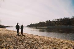 Allegro amandosi baci delle coppie Passeggiata sulla sponda del fiume e sull'abbraccio Immagini Stock