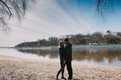 Allegro amandosi baci delle coppie Passeggiata sulla sponda del fiume e sull'abbraccio Immagine Stock