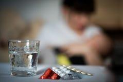 Allein erziehende Mutter-Konzept mit ihrem Kind und farbigen Pillen auf Vordergrund Haben Sie Krise Lizenzfreie Stockfotografie
