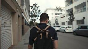 Allein geht Mann entlang Stadtgebäude und -straßen am Sommertag, hintere Ansicht stock footage
