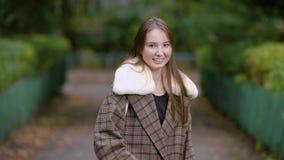 Allein hübsche Brunettefrau steht auf einer Straße in der Gasse im Park am Herbsttag, am Lachen und an beweglichen Händen stock video