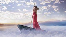 Allein intelligente Frau, die in den Wolken schaufelt Stockfotos