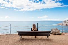 Allein junge Frau, die auf der Bank sitzt Lizenzfreies Stockbild