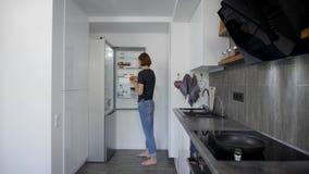 Allein junge Frau erhält Eier vom Kühlschrank in ihrer Küche am Morgen und bereitet sich für das Kochen des Frühstücks vor stock footage