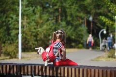 Allein kleines Mädchen mit einem Rucksack, der auf einer Bank im Park sitzt stockbilder