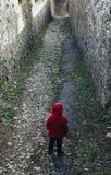 allein Kleinkind mit rotem Mantel im dunklen Straßentunnel der nebelhaften Tunnelwegweise mit hellem Licht lizenzfreies stockbild