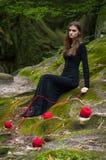 Allein schönes Mädchen sitzt auf grünem Moos in einem feenhaften Wald stockfotografie