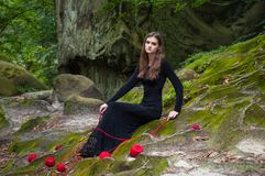 Allein schönes Mädchen sitzt auf grünem Moos in einem feenhaften Wald stockbilder