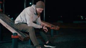 Allein sitzt Mann auf Sportausrüstung im Park nachts und benutzt smartwatch stock video footage