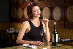 Allein stehende Frau auf einem Datum mit dem Weinglas, das an der Restaurantweinkellerei flirtet Stockfoto