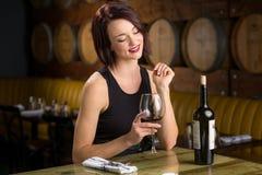 Allein stehende Frau auf einem Datum mit dem Weinglas, das an der Restaurantweinkellerei flirtet Stockbilder
