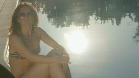 Allein stehende Frau, die nahe Pool bei Sonnenuntergang sitzt Sommer, magische Stunde stock footage