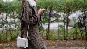 Alleinbrunettemädchen geht auf nasse Straße des Herbstes in der Stadt nach Regen in der Tageszeit und schreibt auf ihrem Smartpho stock footage