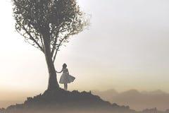 Alleine Frau unter einem Baum, der eine mystische und andeutende Landschaft betrachtet stockfotografie