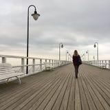 Alleine junge Frau, die auf Pier geht Lizenzfreie Stockbilder