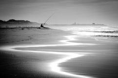Alleiner Fischer auf Strand bei Sonnenuntergang Stockbild