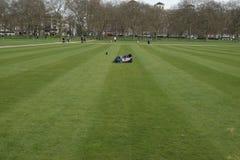 Alleiner Mann, der auf Hyde Park-` s Gras legt Stockfotografie