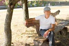 Alleiner Mann von mittlerem Alter, der auf einer Bank sitzt Stockbilder