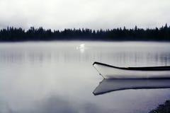 Alleines alaskisches Kanu in einem nebeligen See Stockbilder