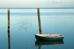 Alleines kleines Boot festgemacht bei Sonnenaufgang lizenzfreie stockfotografie