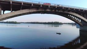 Alleinfischer in einem Boot unter der Brücke stock footage