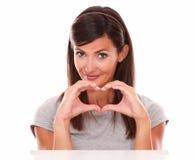 Alleinfrau mit Liebeszeichen lächelnd an Ihnen Stockbild