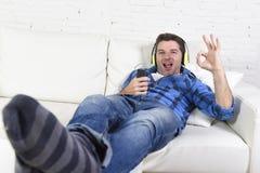 alleinlügen des Mannes 20s oder 30s auf der Couch, die Musik mit Handy und Kopfhörern hört Stockbild